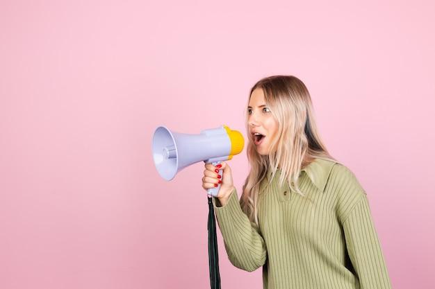 Mulher bonita europeia em suéter casual com megafone na parede rosa