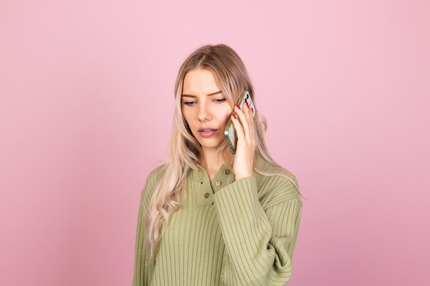 Mulher bonita europeia em suéter de malha casual na parede rosa