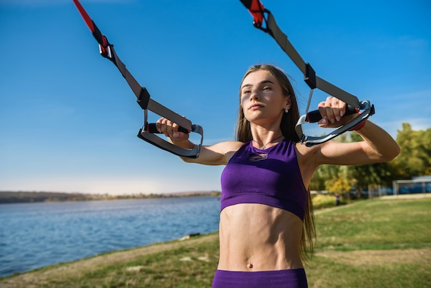 Mulher bonita, exercitando-se com alças de suspensão trx ao ar livre perto do lago durante o dia. estilo de vida saudável