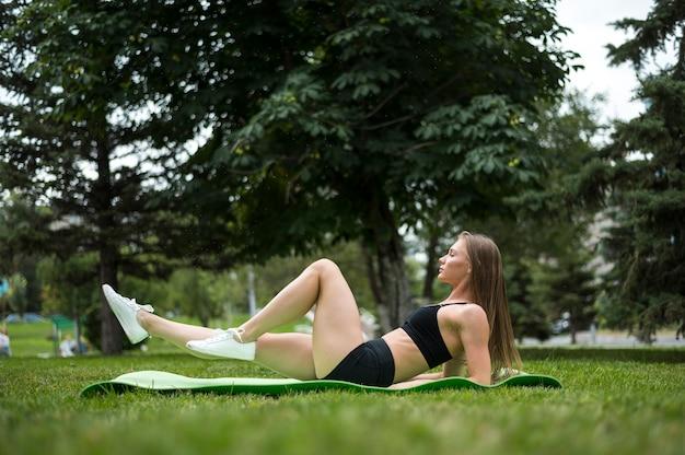 Mulher bonita, exercitando-se na vista de ângulo baixo do parque