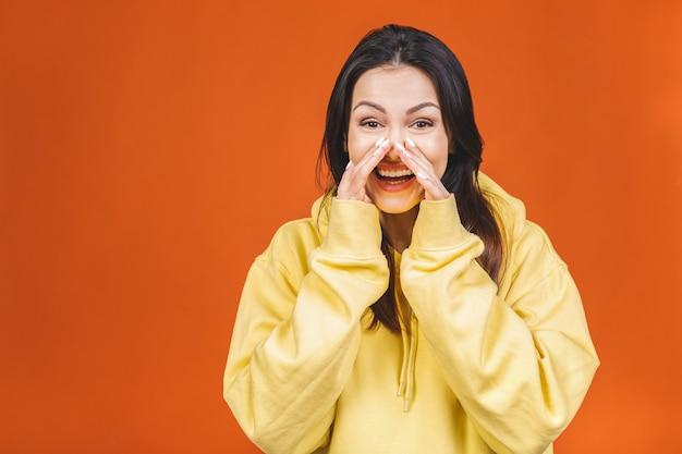 Mulher bonita faladora vestida de casual está dizendo notícias secretas de frenagem quente e olhando para a câmera, isolada em fundo laranja.