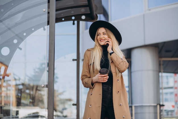 Mulher bonita falando ao telefone e esperando o ônibus
