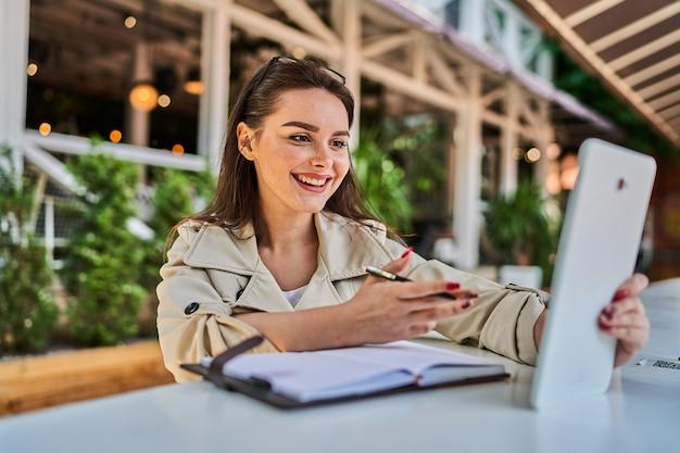 Mulher bonita falando por videochamada com tablet ao ar livre.