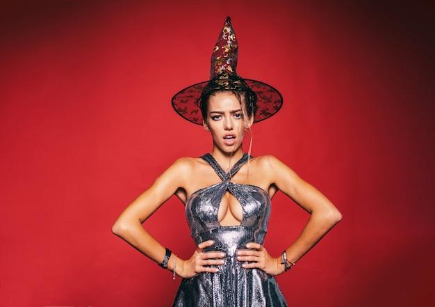 Mulher bonita fantasiada de bruxa na festa de halloween. mulher surpresa com rosto lindo e penteado retrô e lábios vermelhos em estúdio sobre fundo vermelho.