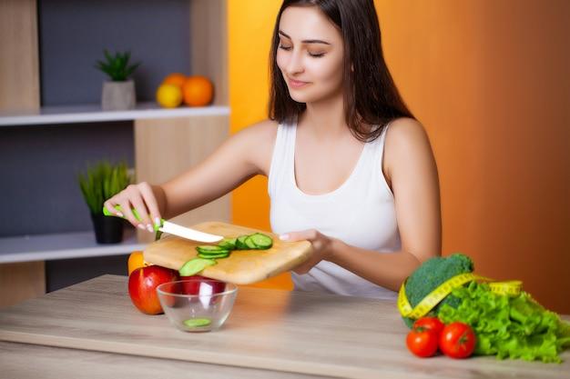 Mulher bonita fatias de pepino para salada de dieta