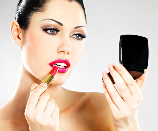 Mulher bonita faz maquiagem aplicando batom rosa nos lábios.