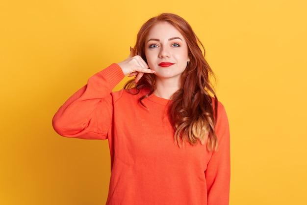 Mulher bonita faz sinal de telefone, diz me liga de volta, se comunica com gestos, vestida de suéter laranja