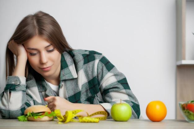 Mulher bonita faz uma escolha entre alimentos saudáveis e prejudiciais