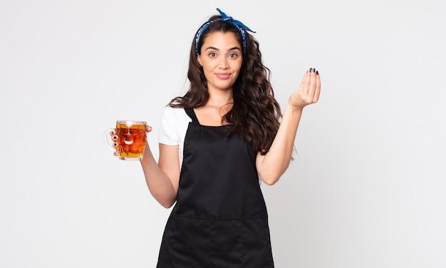 Mulher bonita fazendo capice ou gesto de dinheiro, dizendo para você pagar e segurando um copo de cerveja