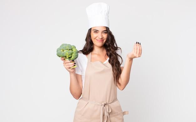 Mulher bonita fazendo capice ou gesto de dinheiro, dizendo para você pagar usando um avental e segurando um brócolis