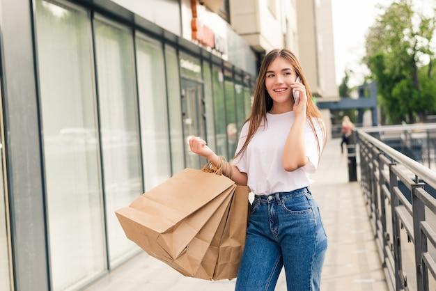 Mulher bonita fazendo compras e falando ao telefone na rua