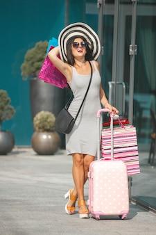 Mulher bonita fazendo compras. menina bonita segurando sacolas de compras e sorrindo. alegre senhora tendo uma viagem.