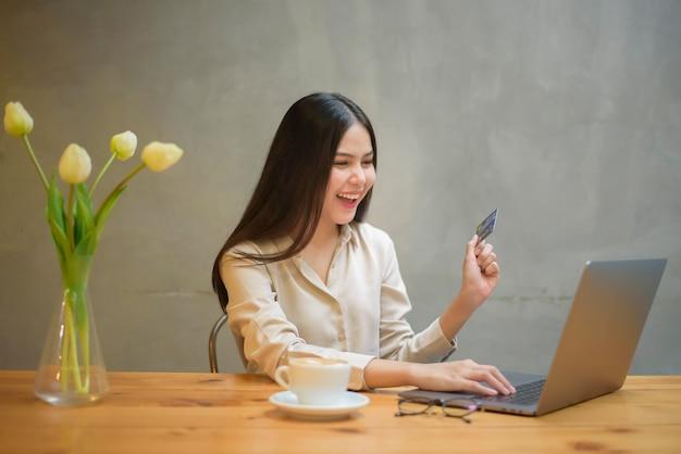 Mulher bonita fazendo compras online com cartão de crédito em uma cafeteria