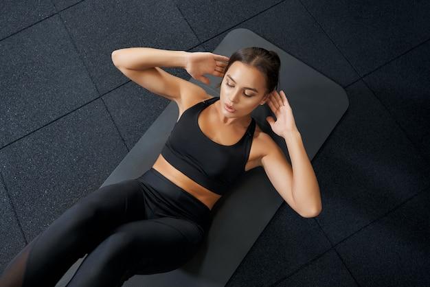 Mulher bonita fazendo exercícios abdominais no tapete