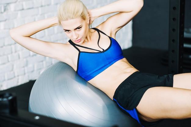 Mulher bonita fazendo exercícios abs em fitball