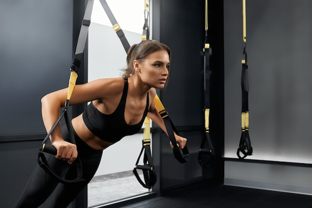 Mulher bonita fazendo exercícios com sistema trx