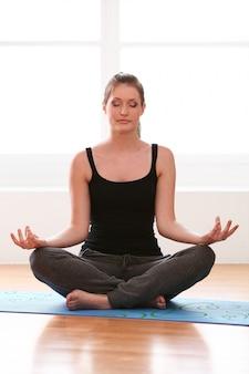 Mulher bonita fazendo exercícios de ioga em casa