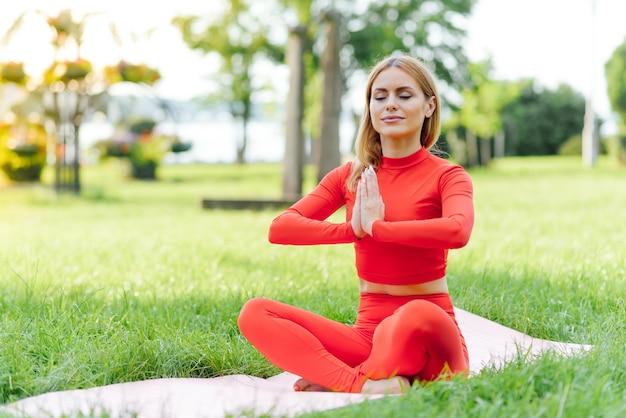 Mulher bonita fazendo exercícios de ioga no parque