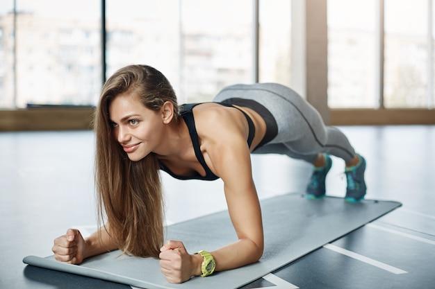Mulher bonita fazendo flexões no ginásio de fitness sorrindo. colocando seu corpo em perfeita forma.