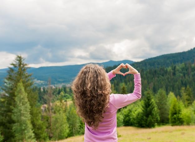 Mulher bonita fazendo gesto de coração no campo de verão