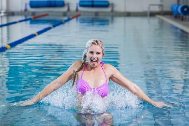 Mulher bonita fazendo hidroginástica na piscina