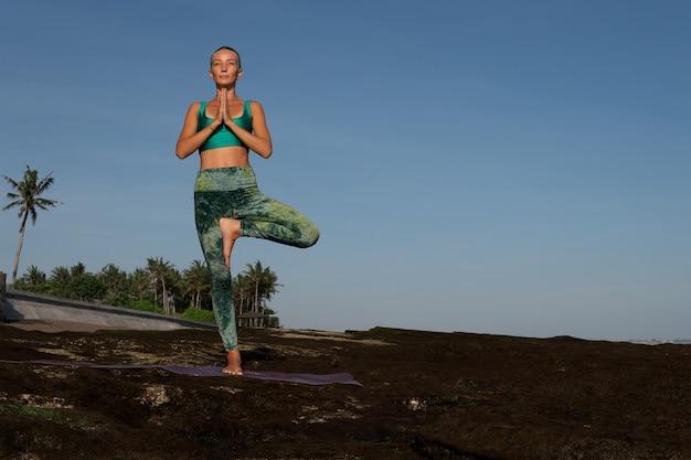 Mulher bonita fazendo ioga. plano do meio