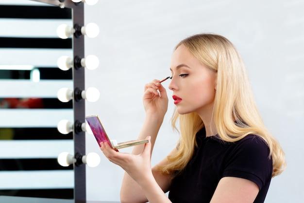 Mulher bonita fazendo maquiagem de noite