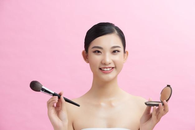 Mulher bonita fazendo maquiagem e segurando o pincel de maquiagem.