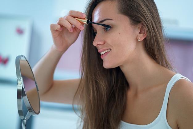 Mulher bonita fazendo maquiagem em casa usando um pequeno espelho redondo e rímel preto de manhã
