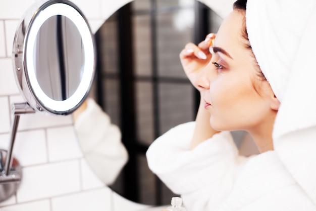 Mulher bonita fazendo procedimentos cosméticos para cuidar da pele do rosto no banheiro