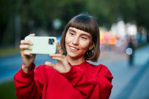 Mulher bonita fazendo selfie na rua moderna, linda mulher milenar em um suéter vermelho elegante, fazendo fotos em seu telefone na cidade moderna backgound