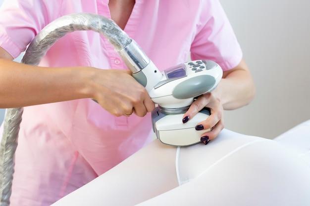 Mulher bonita fazendo terapia estética contra celulite com aparelho de glp