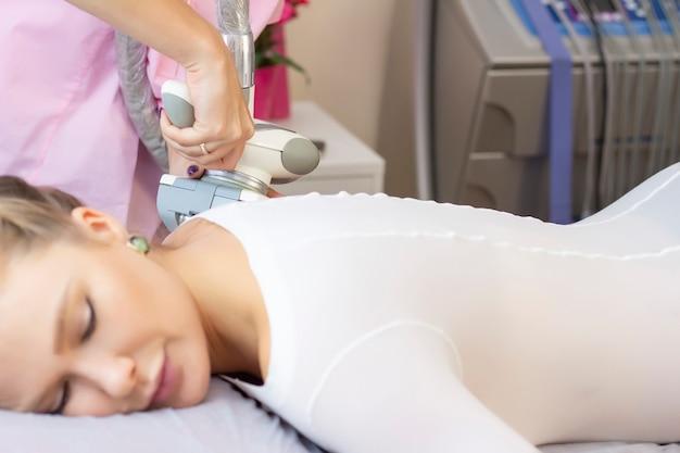 Mulher bonita fazendo terapia estética contra celulite com máquina de glp no bumbum