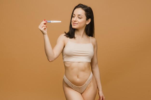 Mulher bonita fazendo teste de gravidez, corpo jovem e em forma posando de roupa íntima