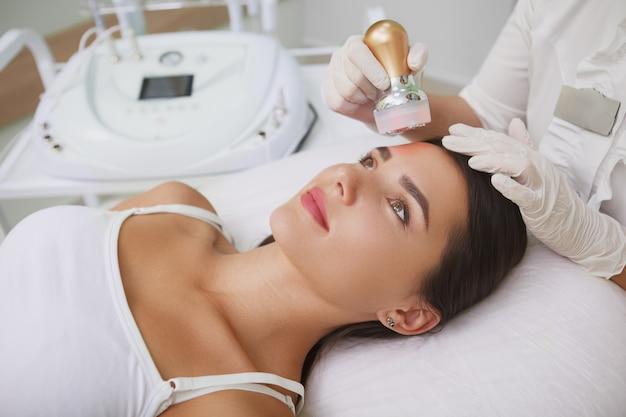 Mulher bonita fazendo tratamento facial para levantamento de rf em clínica de beleza