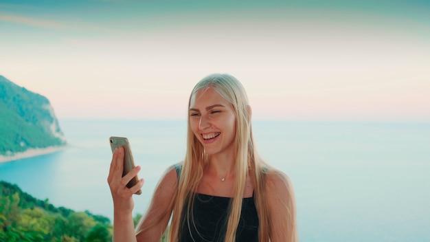 Mulher bonita fazendo videochamada com vista nas férias no mar em países quentes