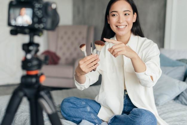 Mulher bonita fazendo vlogs sobre pincéis de maquiagem