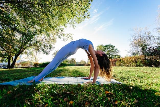 Mulher bonita fazendo yoga em um penhasco, atrás de um incrível pôr do sol no mar