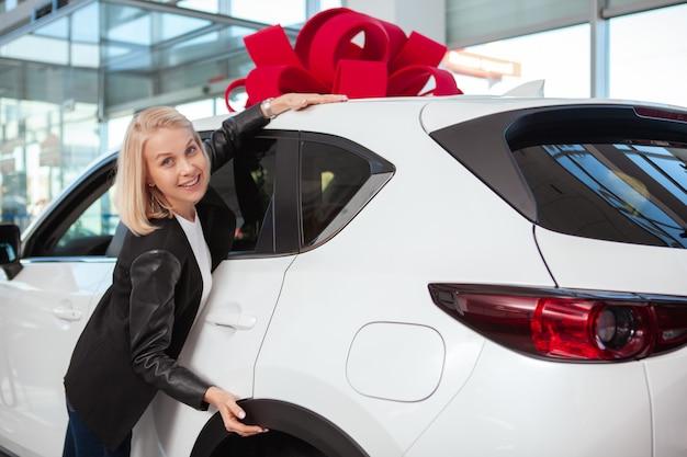 Mulher bonita feliz abraçando seu carro novo com laço vermelho no telhado. alegre motorista do sexo feminino recebendo carro novo como presente na concessionária