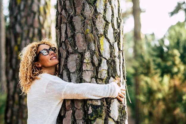 Mulher bonita feliz ama a natureza abraçando um pinheiro