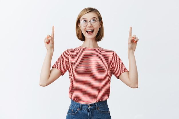 Mulher bonita feliz animada de óculos apontando os dedos e olhando para cima com um sorriso maravilhado