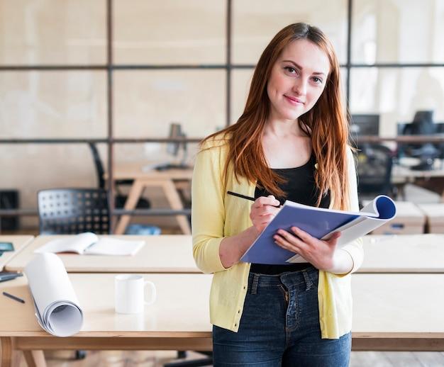 Mulher bonita feliz, apoiando-se na mesa, segurando o livro e lápis no local de trabalho