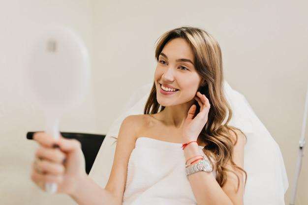Mulher bonita feliz com cabelo longo morena após terapia de cosmetologia, sorrindo para o espelho no quarto branco. alegria, felicidade, bons resultados, verdadeiras emoções positivas