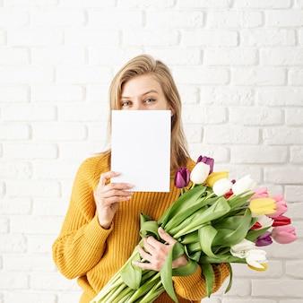 Mulher bonita feliz com roupas amarelas segurando buquê de tulipas e um cartão em branco