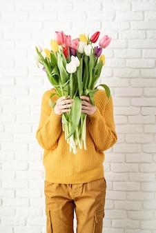 Mulher bonita feliz com roupas amarelas segurando um buquê de tulipas