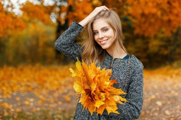 Mulher bonita feliz com um sorriso com flores amarelas de outono no parque