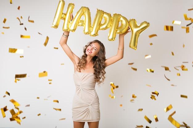 Mulher bonita feliz comemorando o ano novo em confete dourado