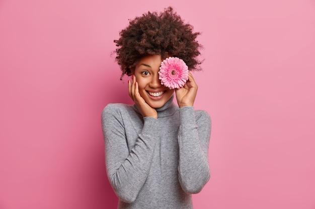 Mulher bonita, feliz, de cabelos cacheados, tem um sorriso alegre, cobre os olhos com uma gérbera, gosta de flores, expressa emoções positivas, vestida de gola olímpica cinza