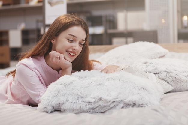 Mulher bonita feliz deitada em uma cama nova na loja de móveis, sorrindo alegremente