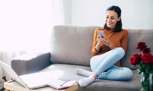 Mulher bonita feliz e animada com telefone inteligente no sofá